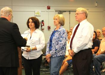 City Council member Bill McGuire presents the Senior Citizens Day proclamation to Deborah Susswein, Kathy Winner and Bill Tol