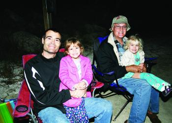 David Rimstidt enjoys the boat parade with daughters, Nicole, 5 and Erica, 3, who sits with her grandfather, Jim Pinkl. PHOTOS BY SHANNA FORTIER