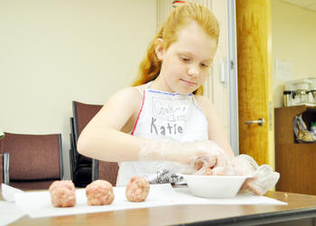 Katie Anderson, 11, rolls meatballs for Italian day. PHOTOS BY SHANNA FORTIER