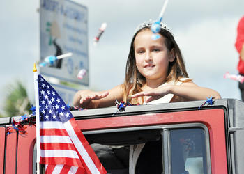 Miss Potato Hannah Blevins throws candy to parade spectators the morning of July 4. PHOTOS BY SHANNA FORTIER
