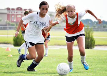 Chasity Vigo and Cara Warren battle for the ball during a one-on-one drill Tuesday morning at the Go To Goal soccer camp.