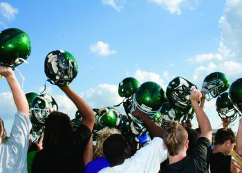 The Buddy Taylor Middle School football players raise their helmets at the end of practice the week before facing Indian Trails in the Belle Terre Bowl. The team ranges in height from 4 feet, 2 inches to 6 feet, 4 inches.