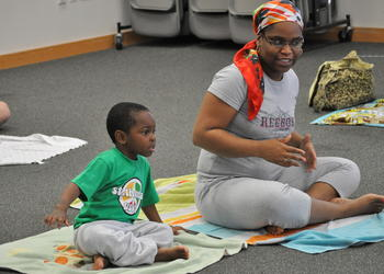 Sheera Jackson and her son Damari stretch to music during yoga at the library, Friday, Feb. 25. PHOTOS BY SHANNA FORTIER