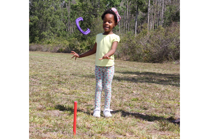 Kyah Fuller, 3, spent part of her time at Bunnell FFA Farm Day Open House honing her horseshoe skills. Photo by Jacque Estes