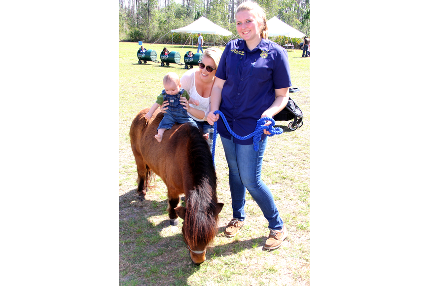 He can'  t walk but Wade Farmer tried out Itty Bitty the FFA miniature horse with a little help from his mom Carla Whitley and FPC student Carley Koehler. Photo by Jacque Estes