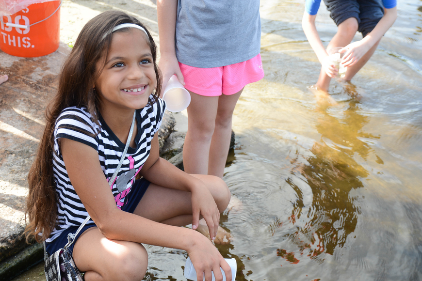 Second-grader Amirah Kardas smiles after releasing a bass into the water. Photo by Paige Wilson