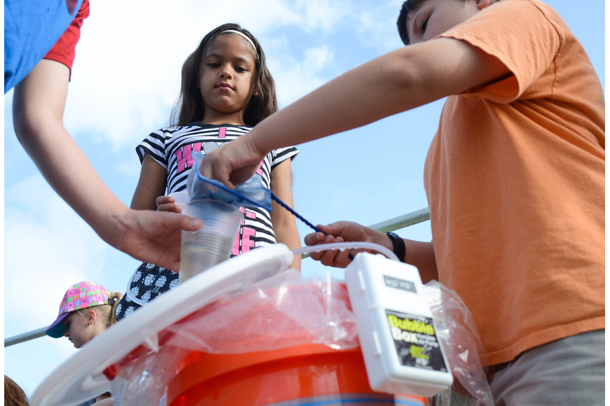 Fifth-grader Austin Weeks, right, plops the bass into a cup full of water. Photo by Paige Wilson
