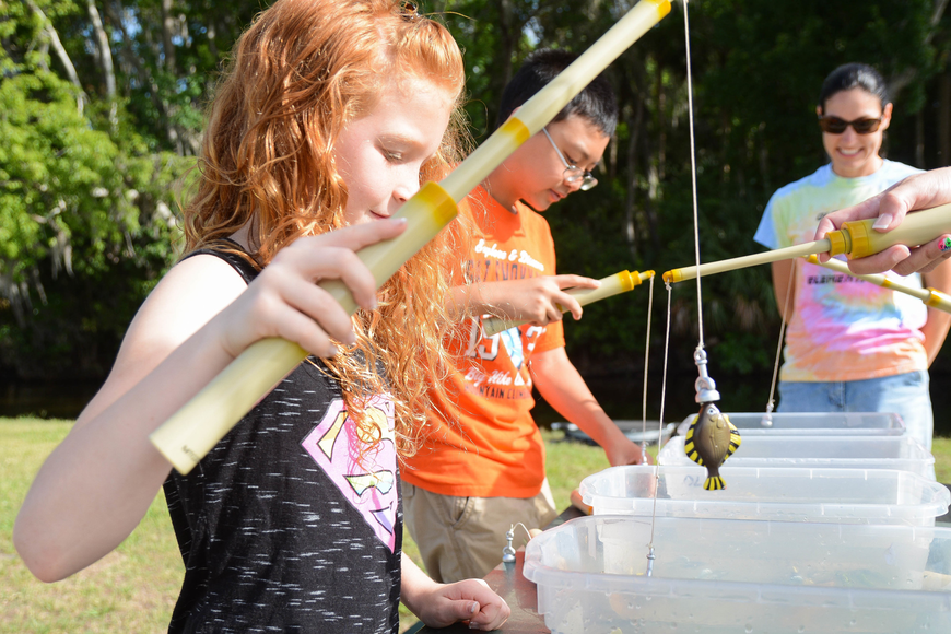 Third-grader Gianna Seifert, left, plays a magnet fishing game. Photo by Paige Wilson