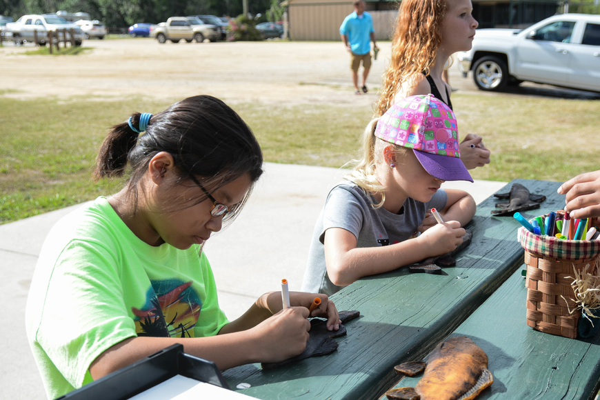 Fifth-grader Glynnis Gong, left, and Allison Sims, middle, color rubber fish as a craft project at the bass release party. Photo by Paige Wilson