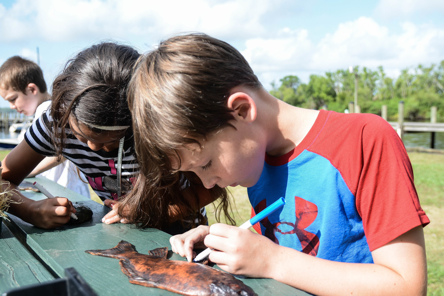 Fourth-grader Aidan Lafferty colors a rubber fish. Photo by Paige Wilson