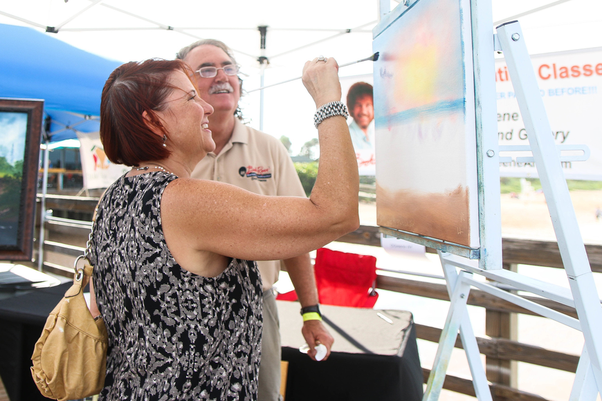 Flagler Beach resident Christine Apetz contributes to a painting on display at the DGreene Art Studio tent. Photo by Paige Wilson