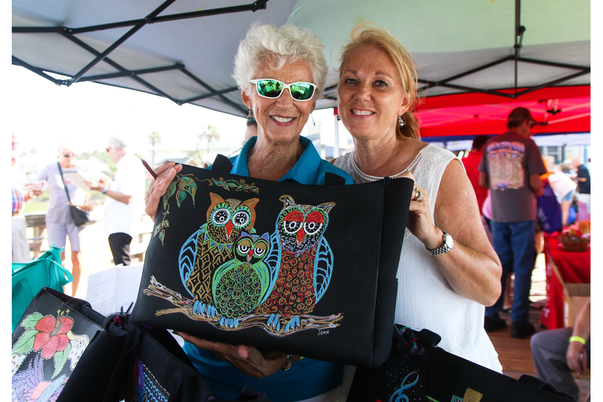 Palm Coast Arts Foundation representatives Joan Mangano and Nancy Crouch hold up a hand-painted bag. Photo by Paige Wilson
