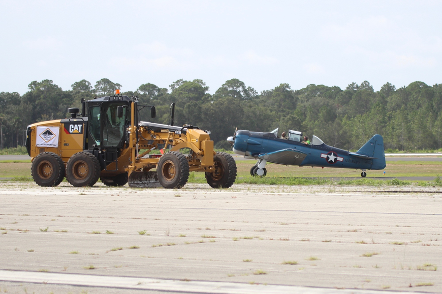 The T-6 Texan returned to the Earth at Flagler Executive Airport's Runway 06-24, the airport's new runway. Construction workers immediately began tearing up the old runway upon takeoff. Photo by Ray Boone