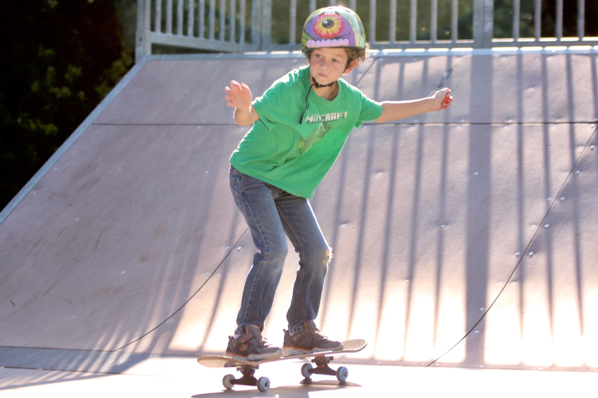Devin Filter, 8, slides down a ramp. Filter has been skateboarding for about a year. Photo by Ray Boone