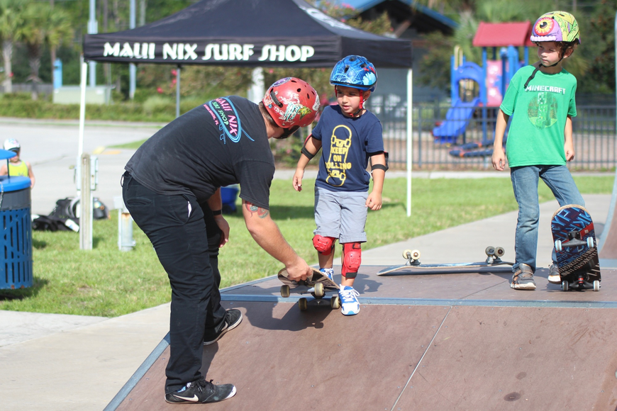 Maui Nix skate team member Dylan O'Keefe (left) instructs 5-year-old Rylan Rookstool (middle) on how to go down a ramp. Photo by Ray Boone