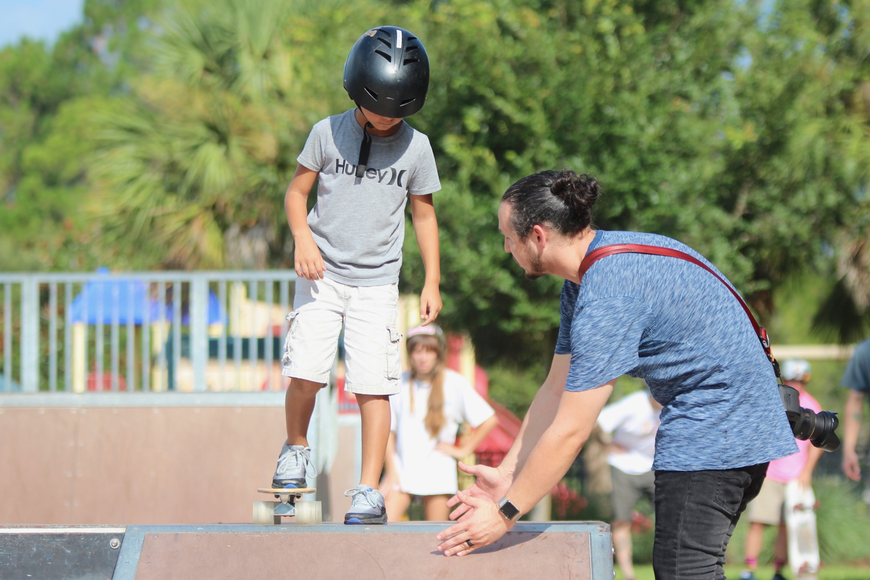 Maui Nix Digital Media Manager Brian Heck helps Julian LeFort, 9, with his skating technique. Photo by Ray Boone