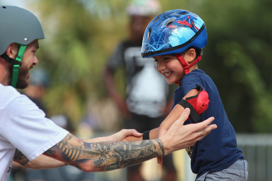 Rylan Rookstool, 5, works on his balance with Maui Nix skater Justin Collins. Photo by Ray Boone