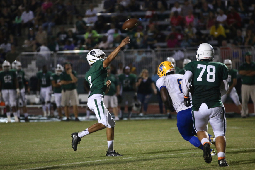 FPC quarterback Ryan Freeman tosses a touchdown pass before getting hit by a Palatka defender. Photo by Ray Boone