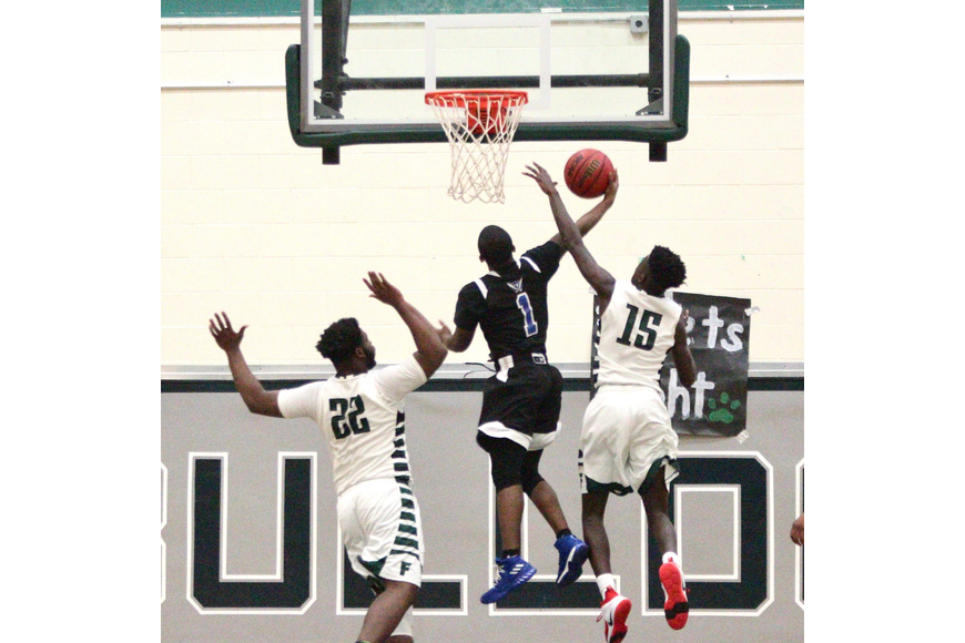 Pirates guard Branden Gilyard gets his shot blocked by FPC's Christopher Fuqua (No. 15). Photo by Ray Boone