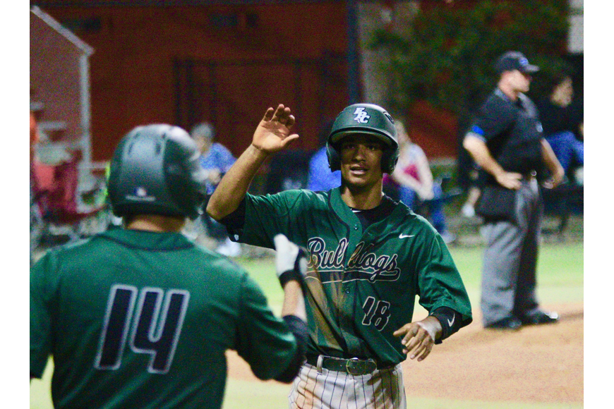 FPC's D'Emiliano Whiters hive-fives a teammate after scoring a run. Photo by Ray Boone