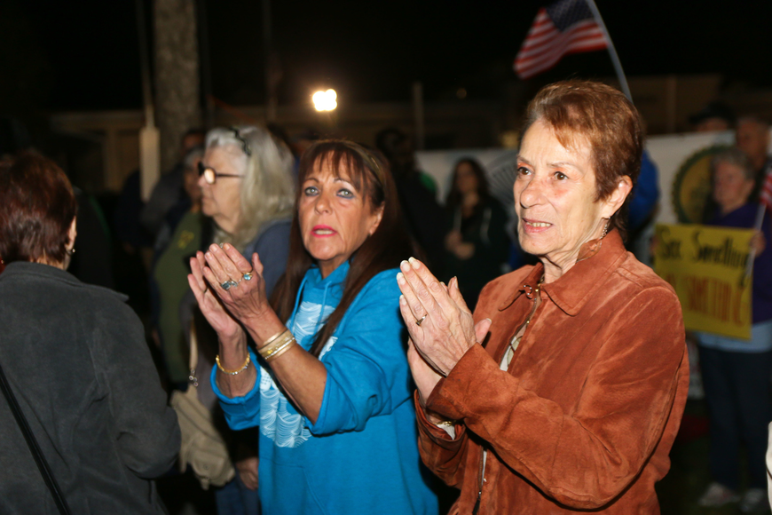 Former Flagler Beach Police Victim Advocate Cheryl Clark and Flagler Beach City Commissioner Jane Mealy applaud after Tyler Perry and other Flagler County students share their message at First Friday. Photo by Paige Wilson