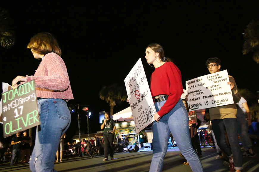 FPCHS SGA President Tyler Perry speaks to the First Friday crowd as students with signs start to line the front of the stage. Photo by Paige Wilson