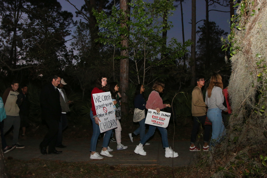 Students leave Wadsworth Park at sunset to start the march over the bridge to Veterans Park. Photo by Paige Wilson