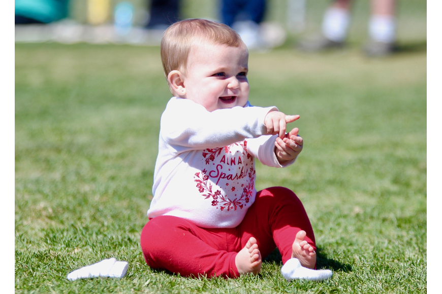 Ten-month-old Brielle Greenslade plays in the grass before a little league game. Photo by Ray Boone