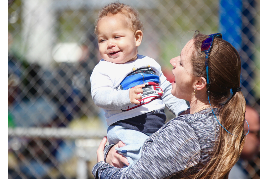 Nine-month-old Kingston Bass smiles at little league opening day. Photo by Ray Boone