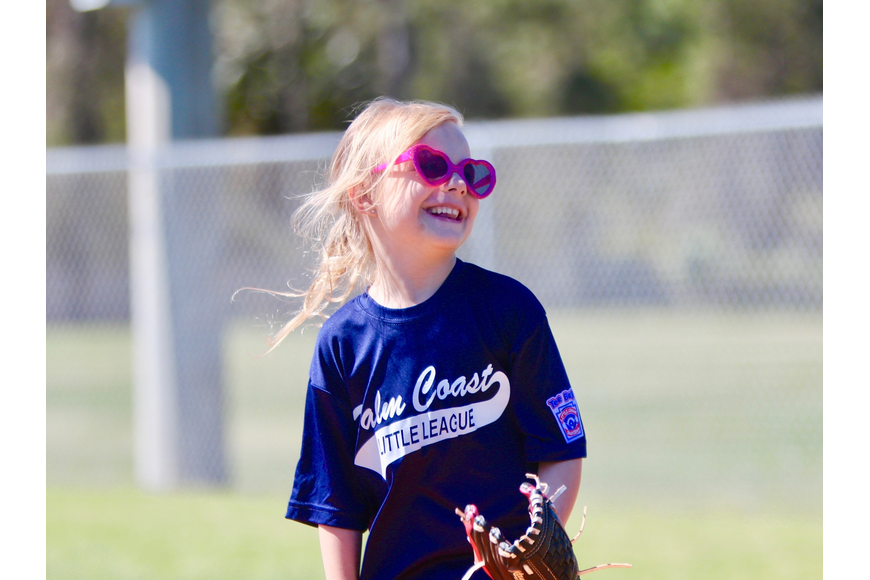 Logan DeRose, 6, smiles at first base during a game. Photo by Ray Boone