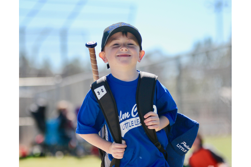 Five-year-old Michael Dolces happily jogs to his little league game. Photo by Ray Boone
