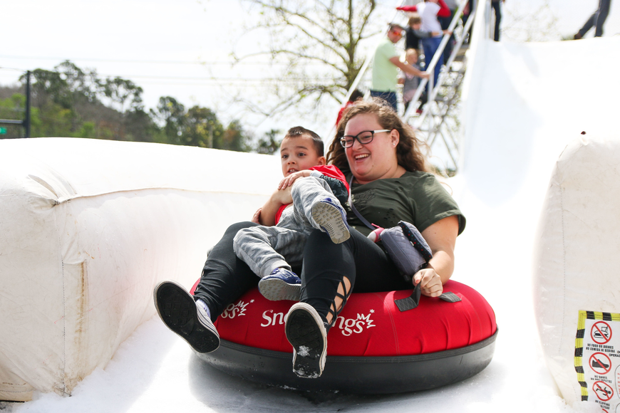 Palm Coast residents Courtney Williams and Cameron Pronesti reach the end of the snow slide. Photo by Paige Wilson