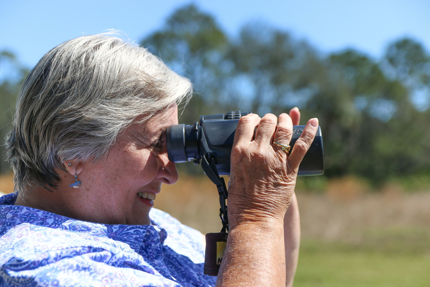 Judie Dziak looks through her Pentax 12x50 binoculars to get a better view of the eagle nest. Photo by Paige Wilson