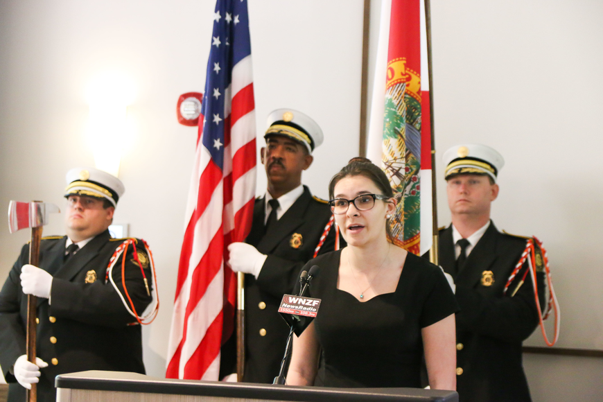 The Palm Coast Fire Department Honor Guard stands behind FPCHS formality singer Kiona Lane as she sings the National Anthem. Photo by Paige Wilson
