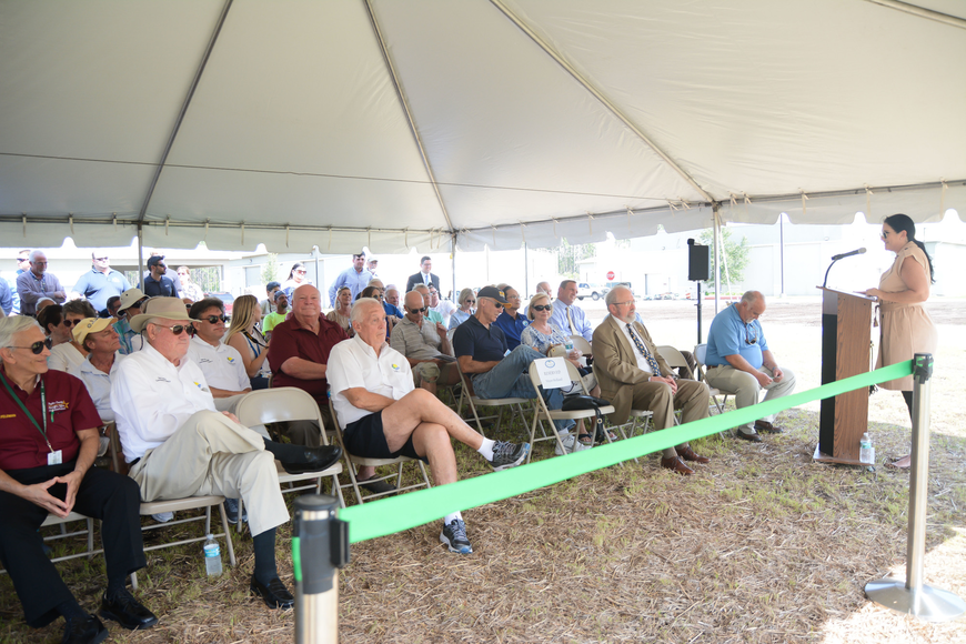 A crowd is gathered under a tent outside Wastewater Treatment Plant 2 for a grand opening ceremony. Photo by Paige Wilson