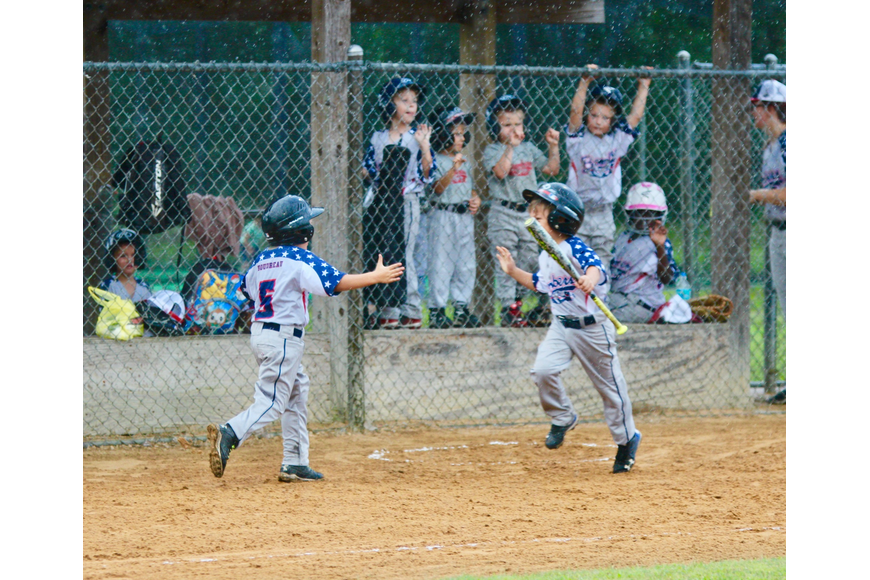 Flagler's Kaiden Boudreaux (No. 5) gives a high five to a teammate after scoring a run. Photo by Ray Boone