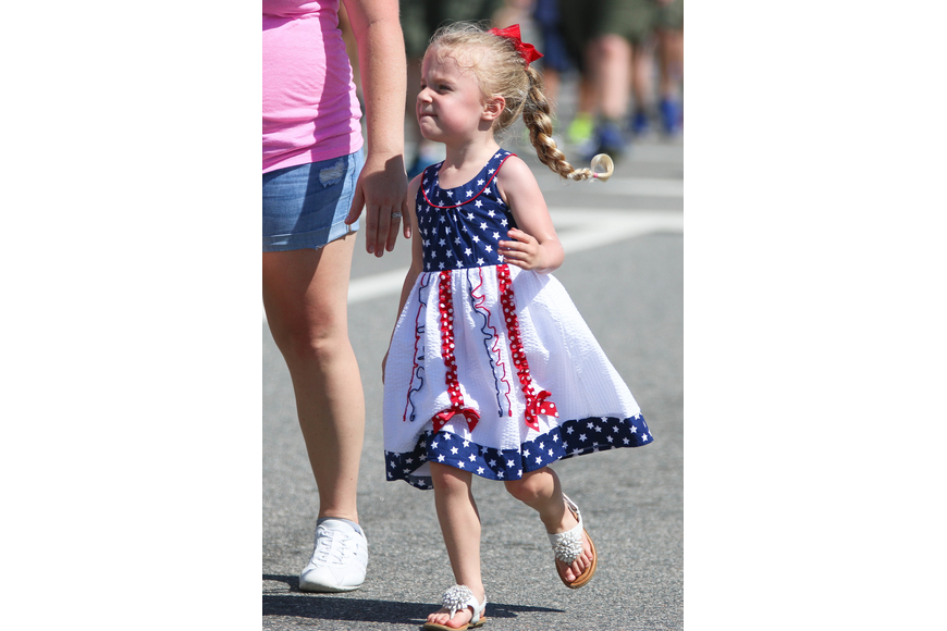 A girl runs by in patriotic attire. Photo by Paige Wilson