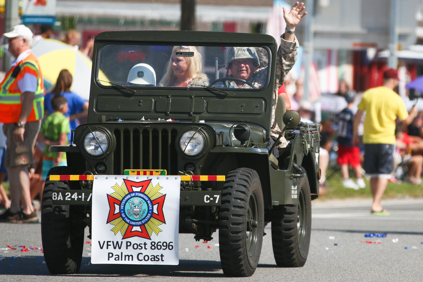 Members of the VFW Post 8696 of Palm Coast ride by in a vintage car. Photo by Paige Wilson