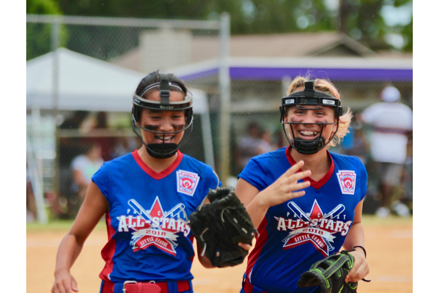 Chloe Baker and Joan Bailey smile as they make their way to the dugout. Photo by Ray Boone