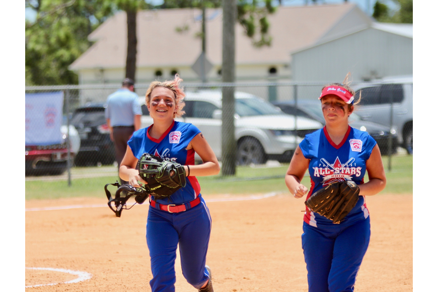 Two Palm Coast softball players smile as they jog toward the dugout after closing out an inning. Photo by Ray Boone