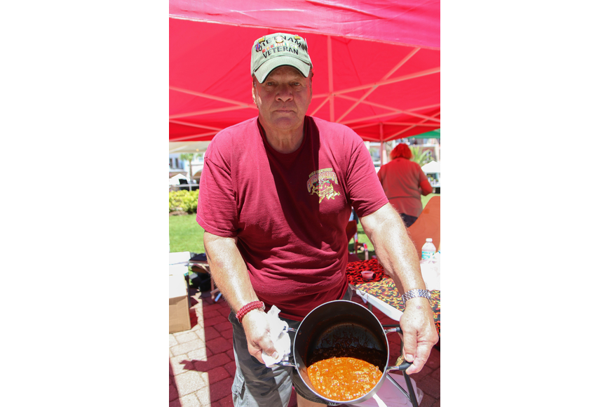 Palm Coast resident Larry Weltikol holds up his homestyle chili. Photo by Paige Wilson