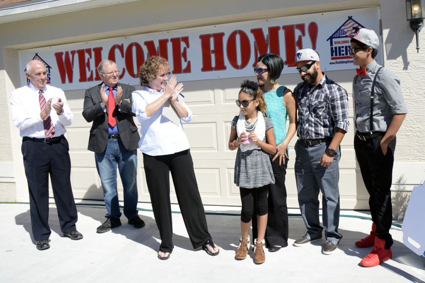 County Commissioner Charlie Ericksen, Vice Mayor Bill McGuire and Florida Event Coordinator Kim Valdyke welcomes the De Leon family to their new home.  Photos by Anastasia Pagello