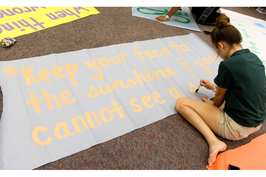 FPC SGA Secretary Madi Bitner paints a quote by Helen Keller: