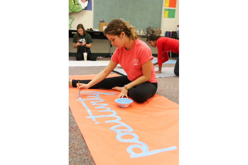 FPC SGA Public Relations Director Alyssa Santore writes a message of positivity on her banner. Photo by Paige Wilson