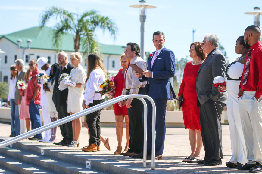 Tom Bexley, Flagler County clerk of the Circuit Court and Comptroller, leads the ceremony for the eleven couples gathered at the courthouse to get married on Thursday, Feb. 14. Photo by Paige Wilson