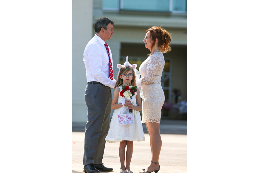 Mia Rose Oliva stands as the flower girl for the ceremony. She stands in front of her father, Carlos Oliva, who is marrying Nina Heikkinen. Photo by Paige Wilson