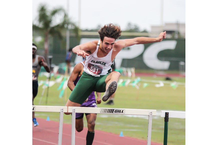 The Bulldogs' Nathan Farrell leaps over the final hurdle on his way to first place in the 300-meter hurdles. Photo by Ray Boone