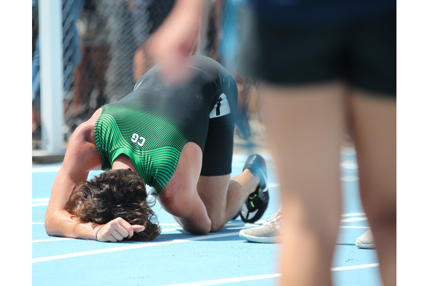 FPC's Nathan Farrell collapses to the ground injured after falling over a hurdle during the 300-meter hurdle final. Photo by Ray Boone