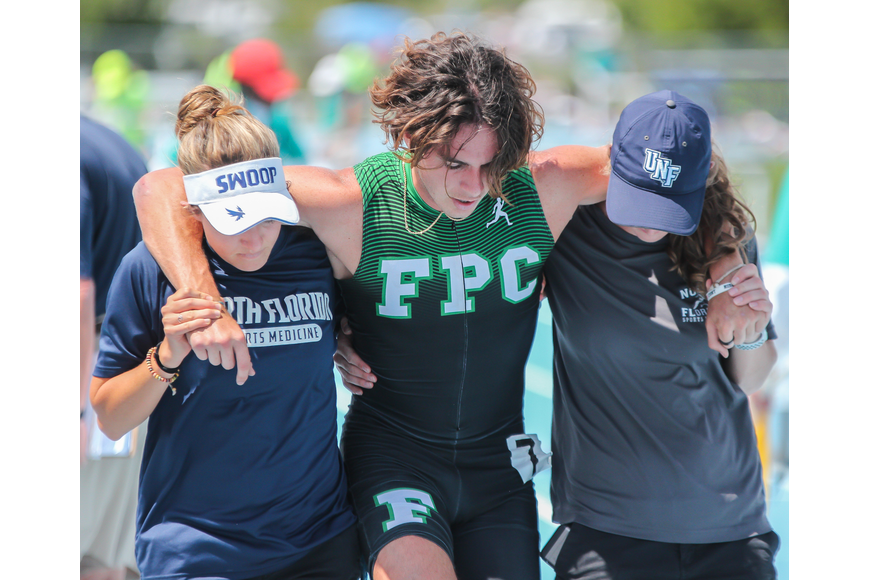 The Bulldogs' Nathan Farrell is carried off the track after taking a fall during the 300-meter hurdle final at the FHSAA track and field state championships. Photo by Ray Boone