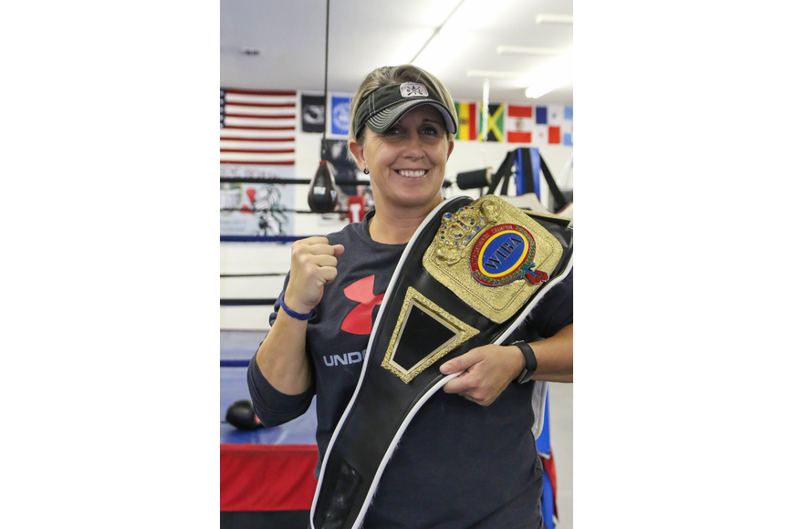 Shelley Burton holds up the belt she won on Nov. 18, 2005: the Women's International Boxing Association's Intercontinental Super Middleweight title. Photo by Paige Wilson